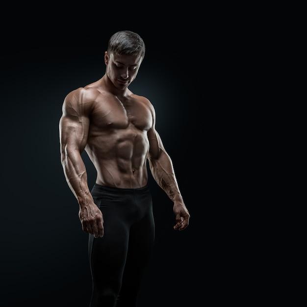Fit Jeune Bodybuilder Posant Sur Fond Noir Photo Premium