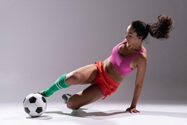 Fit jeune femme avec ballon de foot Photo gratuit