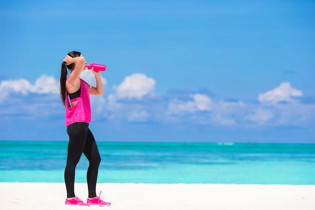 Fit jeune femme boire de l'eau sur la plage blanche Photo Premium