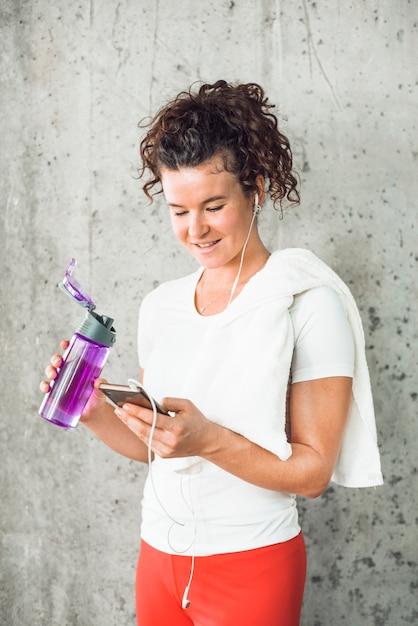 Fit Jeune Femme Avec Une Bouteille D'eau à L'aide De Téléphone Portable Photo gratuit