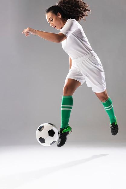 Fit jeune femme jouant au football Photo gratuit