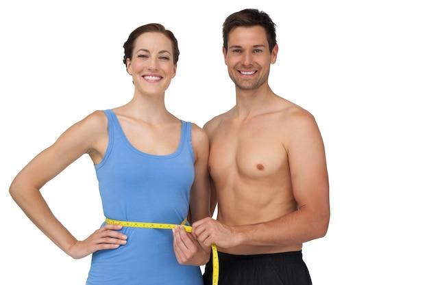 Fit jeune homme mesurant la taille des femmes Photo Premium