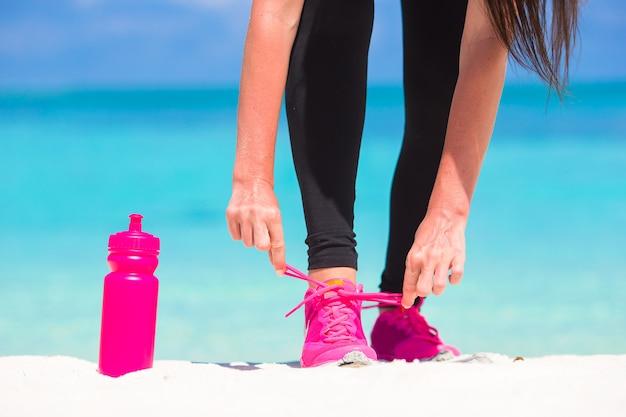 Fitness Et Concept De Mode De Vie Sain Avec Un Modèle Féminin Attachant Des Lacets Sur Des Baskets Photo Premium