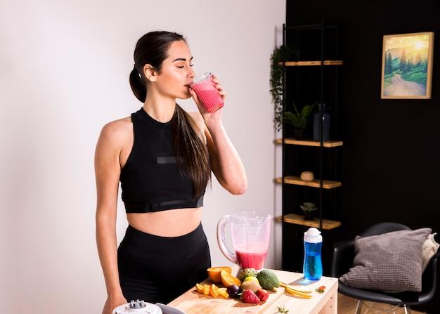 Fitness femme buvant un jus de désintoxication Photo gratuit