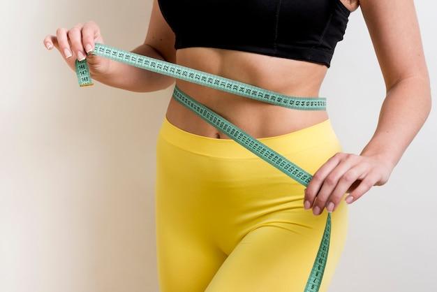 Fitness femme avec un ruban de mesure Photo gratuit