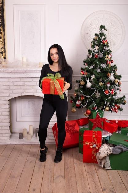 Fitness femme en vêtements de style sport avec boîte-cadeau de noël dans ses mains près de sapin de noël Photo Premium