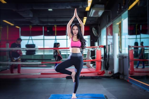 Fitness femmes asiatiques pratiquant la formation de yoga à l'intérieur de la salle de sport et au club de santé Photo Premium