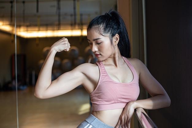 Fitness femmes montrent les muscles des bras dans la salle de gym. Photo gratuit
