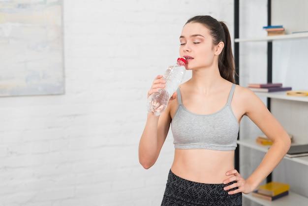 Fitness fille eau potable Photo gratuit