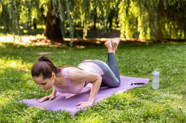 Fitness Girl Pumping Press Sur Le Plein Air Et Un Parc Photo gratuit