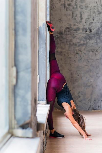 Fitness Jeune Femme D'affaires Se Penchant Près De La Fenêtre, Pratiquer Le Yoga Photo gratuit