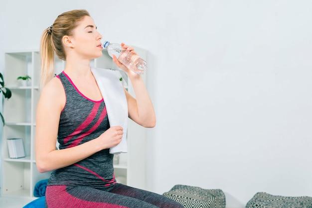 Fitness jeune femme dans une bouteille de vêtements de sport Photo gratuit
