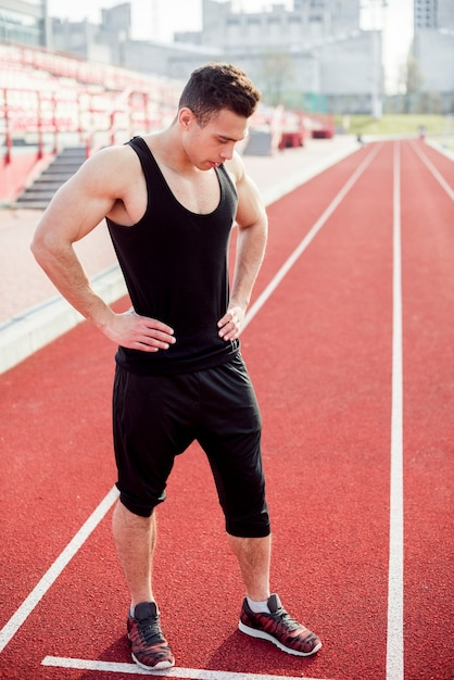 Fitness jeune homme debout sur la piste Photo gratuit