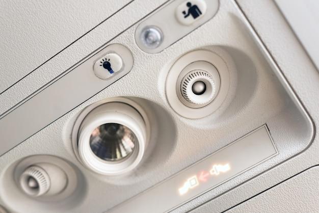Fixez le voyant de ceinture de sécurité et le panneau de la console au climatiseur situé au-dessus du siège dans la cabine d'un avion commercial à faible coût. Photo Premium