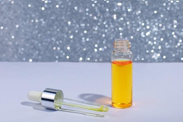Flacon cosmétique ou médical avec pipette. produit liquide doré dans une bouteille en verre avec compte-gouttes. Photo Premium