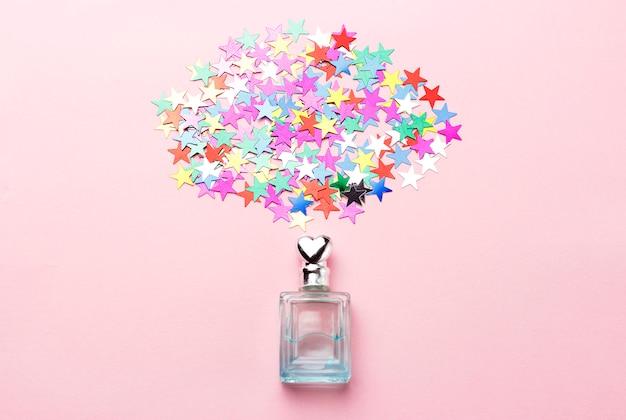 Flacon de parfum et confettis sur fond rose, poser à plat Photo Premium