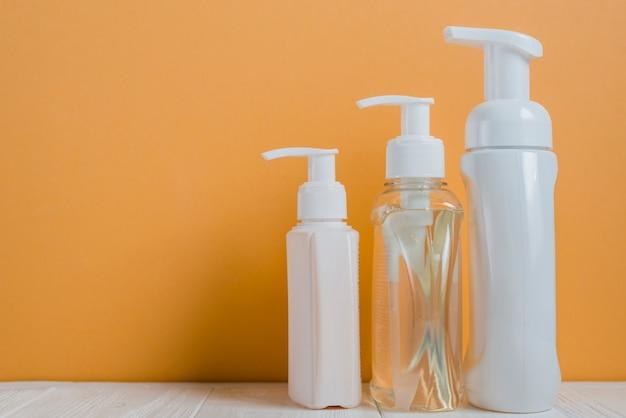 Flacons distributeurs de savon transparents et blancs sur un fond orange Photo gratuit