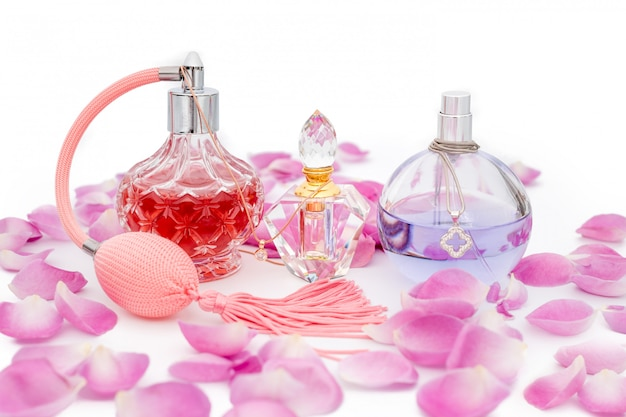 Flacons de parfum avec colliers parmi les pétales de fleurs. parfumerie, cosmétique, collection de parfums Photo Premium