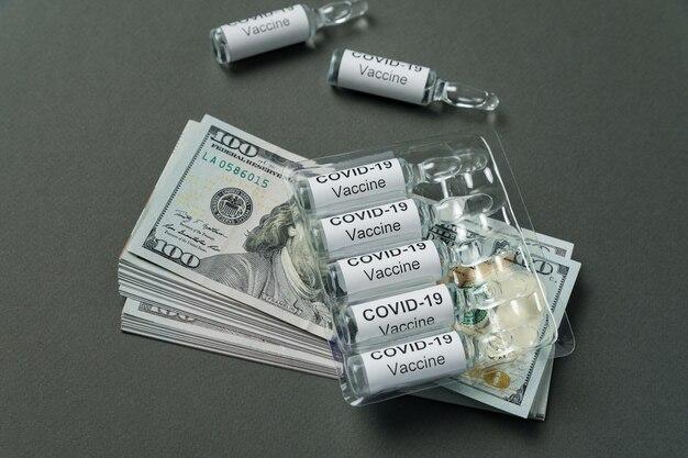 Des Flacons De Vaccin Contre Le Coronavirus Reposent Sur Une Pile De Dollars. Prix Des Médicaments De Covid-19. Photo Premium