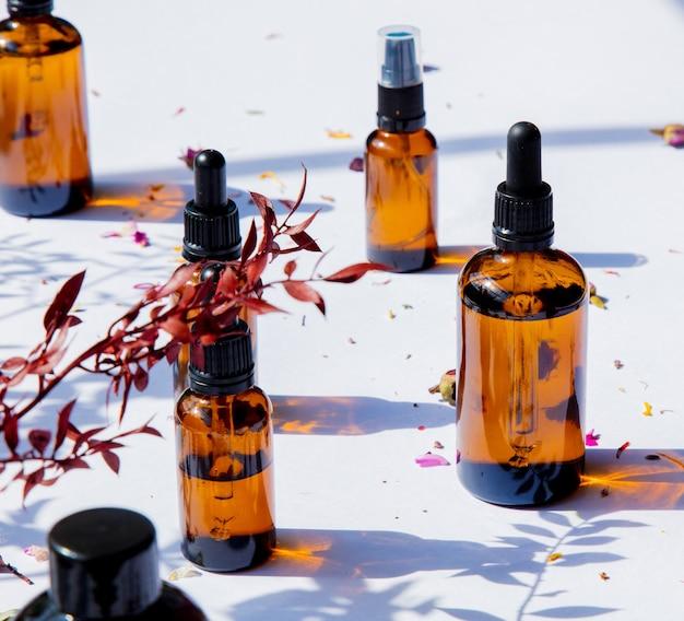 Flacons En Verre De Parfumeur Avec Des Parfums Sur Une Surface Blanche. Photo Premium