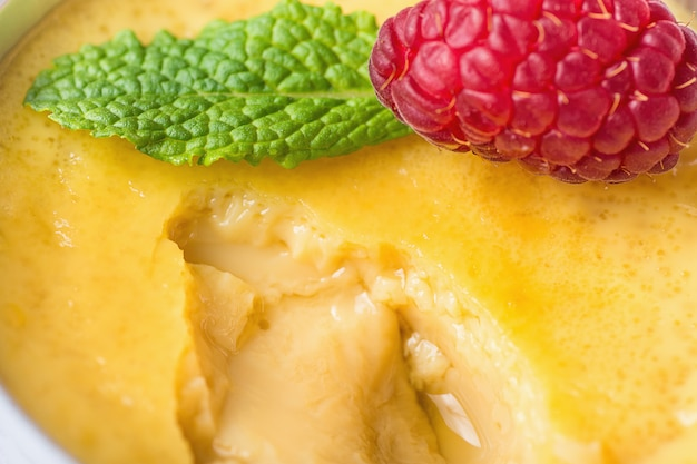 Flan de crème pâtissière aux œufs de vanille sucrée avec framboise fraîche et menthe dans une tasse à portion ramassée. Photo Premium
