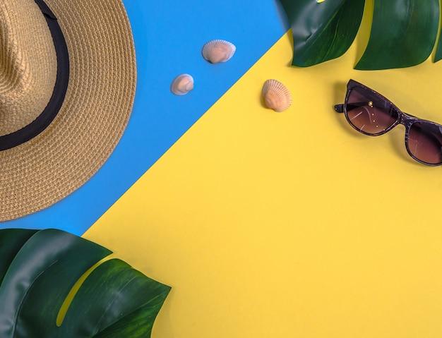 Flatlay avec des feuilles de monstera, chapeau de paille et autres accessoires Photo Premium