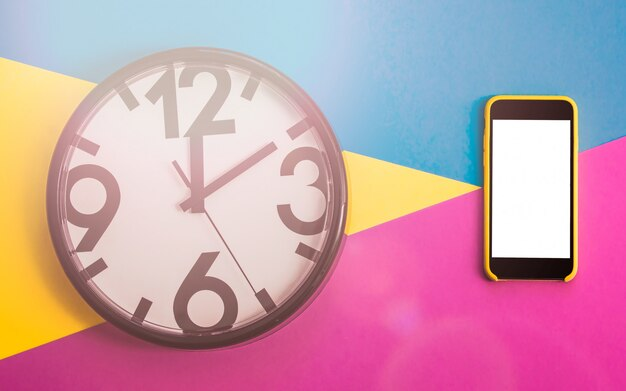 Flatlay avec horloge et clavier sur trois tons de couleur unie jaune, violet et bleu clair Photo Premium