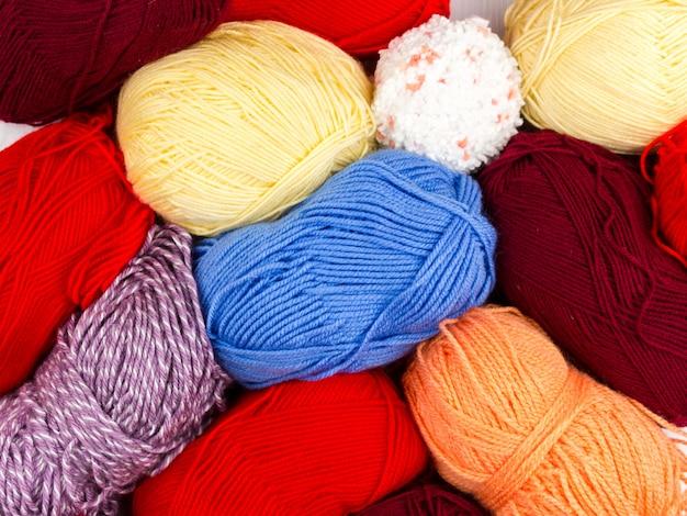 Flatlay de pastilles multicolores tricotant des écheveaux de laine et des aiguilles à tricoter sur fond blanc Photo Premium