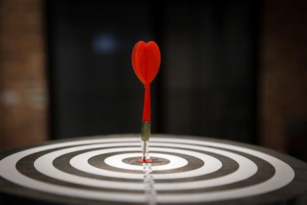 Flèche de cible de fléchette rouge frappant sur bullseye Photo Premium