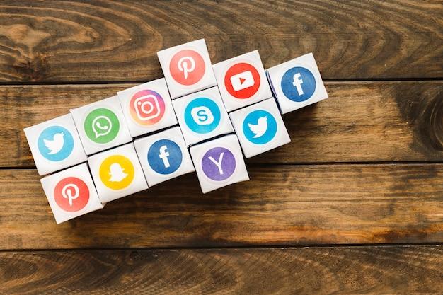 Flèche faite avec des boîtes d'icônes de médias sociaux vives sur une planche en bois Photo gratuit