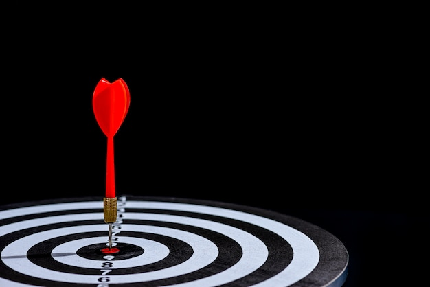 La flèche de fléchette rouge frappant au centre de la cible est un jeu de fléchettes sur fond noir Photo Premium