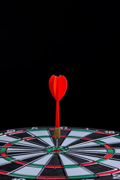 Flèche Fléchette Rouge Frapper Dans Le Centre Cible Est Le Jeu De Fléchettes Sur Fond Noir Photo Premium