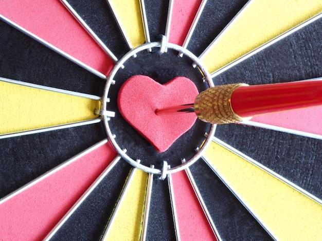 Une flèche rouge fléchette frapper au centre de la cible Photo Premium