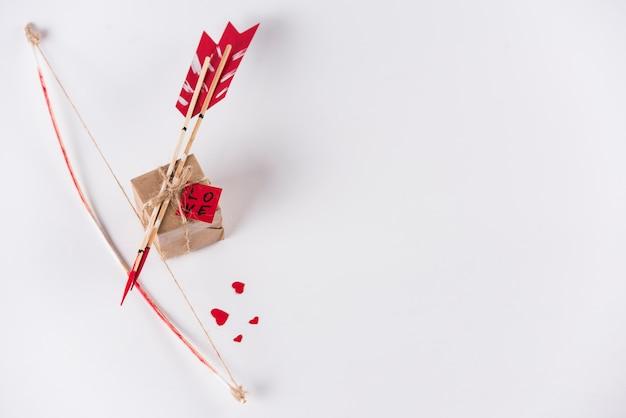 Flèches D'amour Avec Un Arc Et Une Boîte Cadeau Sur Une Table Blanche Photo gratuit