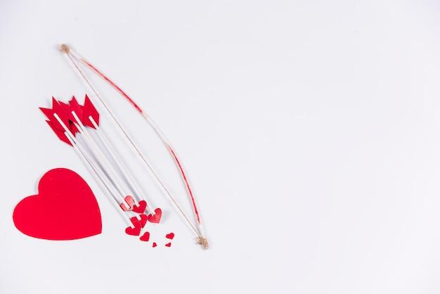 Flèches D'amour Avec Arc Et Coeur Sur Table Photo gratuit
