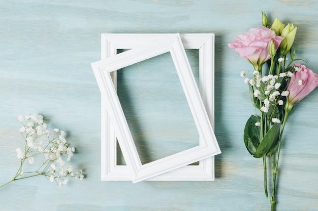 Fleur blanche de souffle de bébé et eustoma près du cadre en bois blanc sur fond de texture bleue Photo gratuit