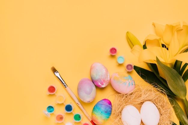 Fleur de lys frais avec des oeufs de pâques colorés; pinceau et aquarelle sur fond jaune Photo gratuit