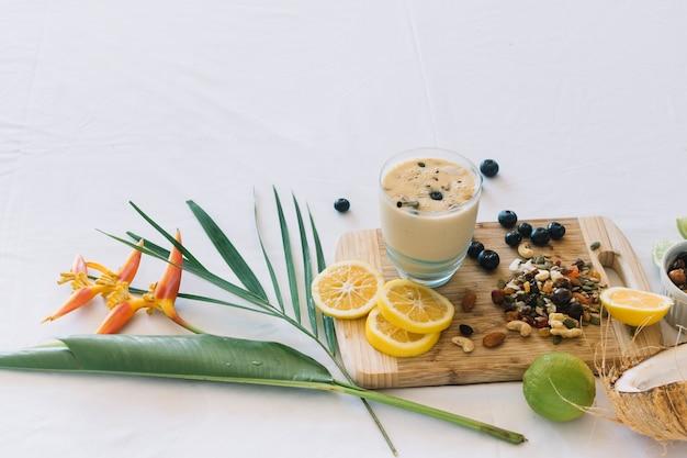 Fleur d'oiseau de paradis; smoothie aux fruits secs et agrumes sur fond blanc Photo gratuit