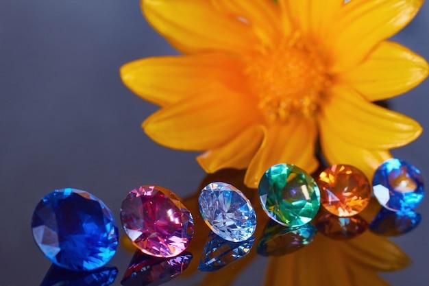 Fleur orange en gros plan et plusieurs cristaux chics sur une surface de miroir noire, scintillant et brillant Photo Premium