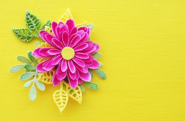 Fleur de papier fait main rose vif et feuilles jaunes et vertes sur un fond jaune vif. espaces à copier. Photo Premium