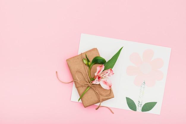 Fleur rose avec une boîte cadeau sur une table rose Photo gratuit