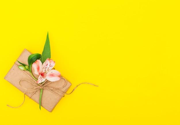 Fleur rose avec coffret cadeau sur table Photo gratuit