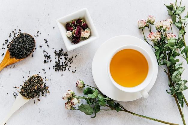Fleur rose séchée aux herbes de thé sur fond de béton Photo gratuit