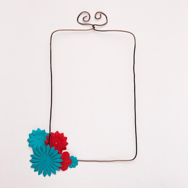 Fleur rouge et bleue sur le coin du cadre rectangulaire filaire sur fond blanc Photo gratuit