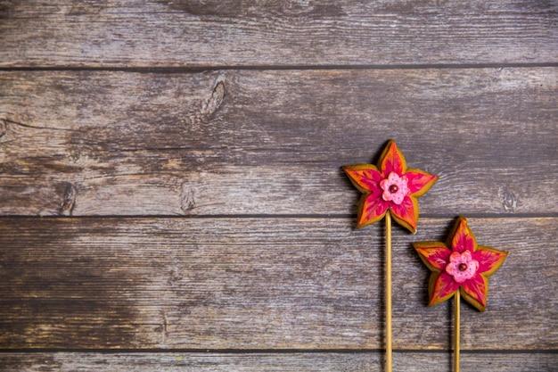 Fleur rouge en pain d'épice peinte à la main sur fond en bois. vue de dessus Photo Premium