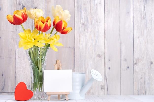 Fleur De Tulipe Dans Un Vase En Verre Avec Décor De Cadre Photo Sur Le Mur De Fond De Table En Bois à La Maison, Gros Plan, Concept De Conception De Fête Des Mères. Photo Premium