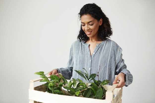 Fleuriste De Belle Femme Transportant Une Boîte En Bois Avec Des Plantes Sur Un Mur Blanc Photo gratuit