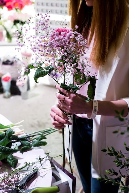 La Fleuriste Crée Un Joli Bouquet De Gypsophile Et De Roses Au Comptoir Du Marché Aux Fleurs Photo Premium