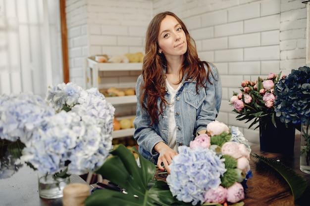 Fleuriste dans un magasin de fleurs faisant un bouquet Photo gratuit