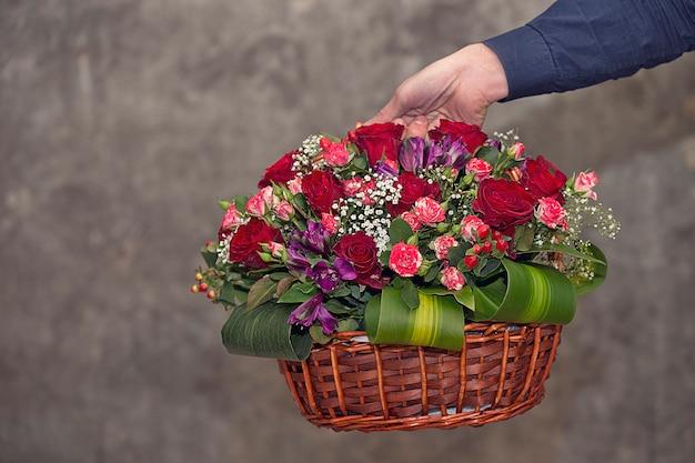 Fleuriste faisant la promotion d'un panier de fleurs mixtes. Photo gratuit